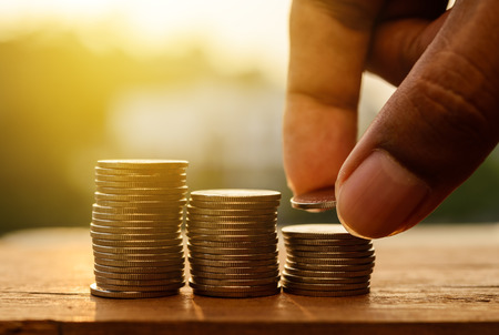 Hand with rows of coins and account for finance and banking concept, Hand with money coin stack growing business, Saving money concept
