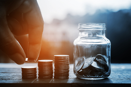 Hand with rows of coins and account for finance and banking concept