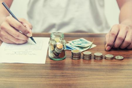 Besparingsgeld en rekeningsbankwezen voor financiën bedrijfsconcept, Mens met stapel van het nutsrekening van het muntgeld op de uitstekende stijl van de bedrijfsbureaulijst Stockfoto