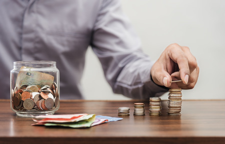 Investor and accountant concept, Saving money and account banking for finance business concept, Business man with coin money on business office table Stock Photo