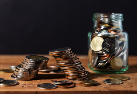 Bankruptcy concept, Saving money and account banking for finance business concept, Coin with bottle on wooden table black background