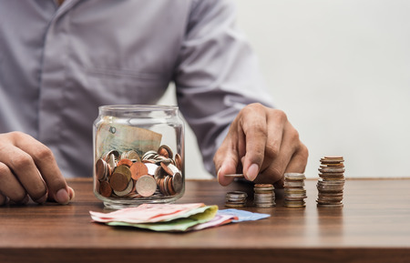 Investor and accountant concept, Save money and account banking for finance business concept, Business man with coin money on business office table Stock Photo
