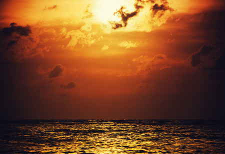 Sky sunset or sunrise with sea and cloud storm over light the sun in twilight dark color tone Stock Photo