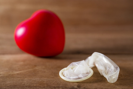 Valentine concept, Condom with red heart on wooden blurred background