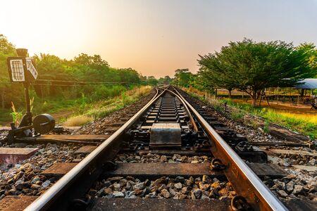 Eisenbahn- und Eisenbahnzugtransport mit Farbe des Himmelssonnenlichts im Waldhintergrund