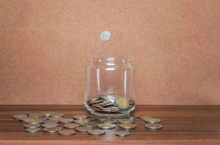 Save money and account banking for finance business concept, Coin in bottle and fall on brown background Imagens