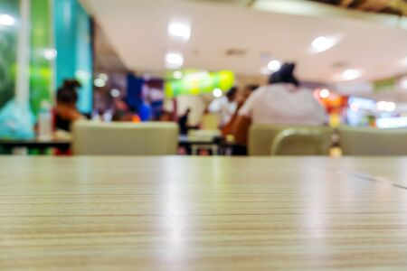 Table in food court at shopping mall blurred background