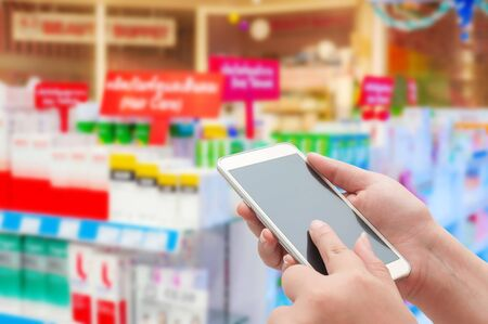 Pharmacy and drugstore concept, Hand women using smart phone in pharmacy store on blurred background