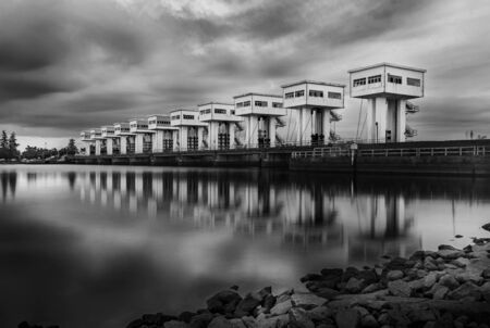 Water barrier with cloud sky in sunset and river long exposure style, Black and white and monochrome style