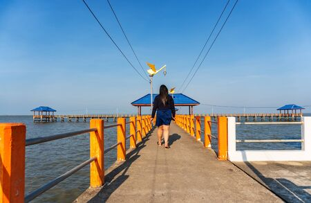 Some people walking on the bridge in the blue sea in evening light