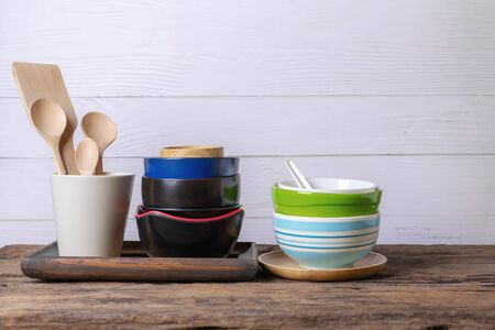Rustic kitchenware against white wooden wall, Ceramic pot with wooden cooking utensil set
