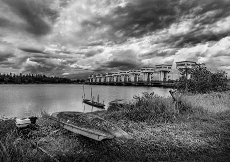 Fishing boat and water barrier and river with cloud sky storm in rain season, Black and white and monochrome style