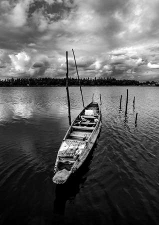 Fishing boat with view of landscape nature in sky and cloud storm and river in stormy rain season, Black and white and monochrome style