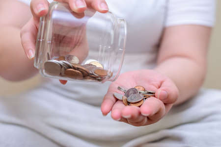 Save money and account banking for finance concept, Hand with coin bottle blurred background