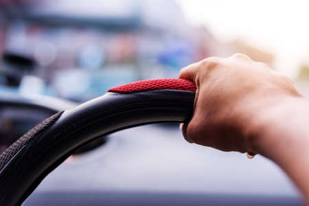 Driving concept, Hand driving a car on the road blurred background Standard-Bild
