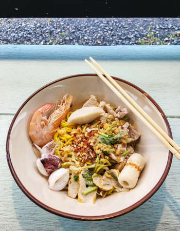 Noodle in a bowl, with shrimp, and squid, and chili, and vegetable, on wooden table, blurred background