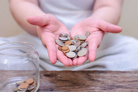 Save money and account banking for finance concept, Hand with coin on blurred background 免版税图像