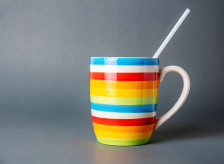 Drinking cup multicolor with white tube on, Gray background, Food and drink concept