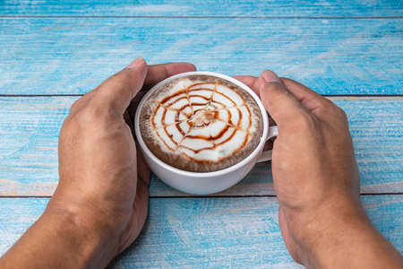 Hand human with latte coffee in a cup of coffee on blurred background Banque d'images