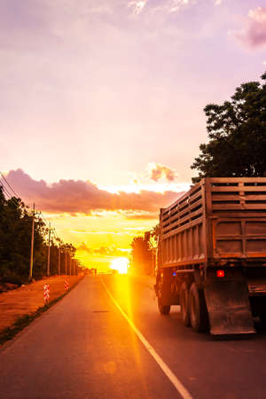 Truck on road with colorful of sunset or sunrise in twilight