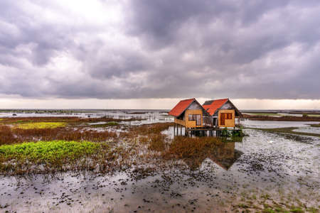 View of an abandoned house in the middle of the lake with sky and cloud rain in sunset 免版税图像