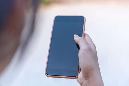Hand women with smart phone black screen blurred background
