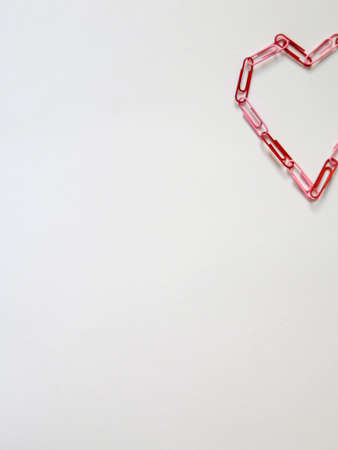 san valentin: Heart made with red clips on a white paper Stock Photo