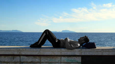 lonely boy: thinking lonely boy lying waterfront