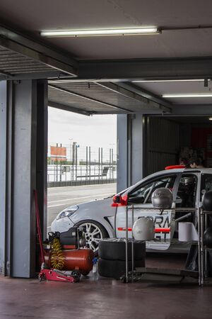 white car in the garage of a racing circuit repaired to run