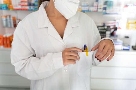 Pharmacist girl holds her pocket where she contains pens to write down prescriptions Banco de Imagens