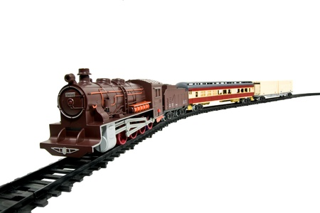 railway transportation: a childs toy train on its tracks isolated on white
