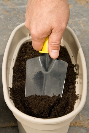 planter: mans hand with a trowel digs in a planter to plant seeds