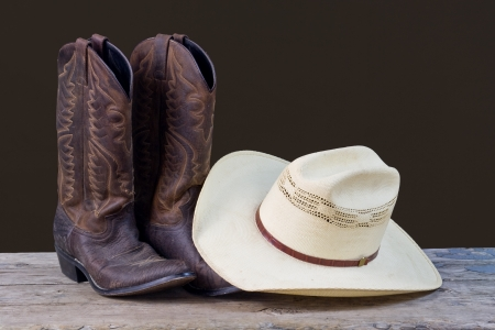 brown leather hat: cowboy boots and cowboy hat on wood floor with brown background