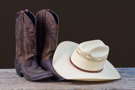 head wear: stivali da cowboy e cappello da cowboy sul pavimento in legno con sfondo marrone