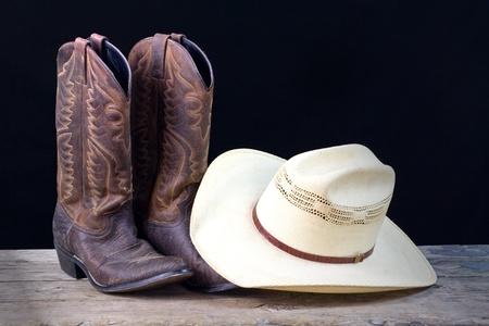 botas vaqueras: botas de vaquero y sombrero de vaquero en suelo de madera con fondo negro Foto de archivo