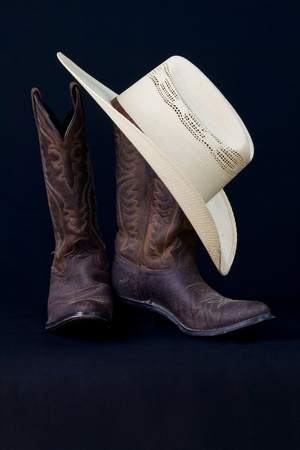 brown leather hat: cowboy boots and cowboy hat with black background Stock Photo
