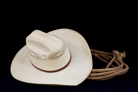 a cowboy hat and lasso on a black background Stock Photo - 9783764