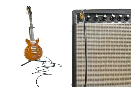 closeup of amplifier and electric guitar in background with cord