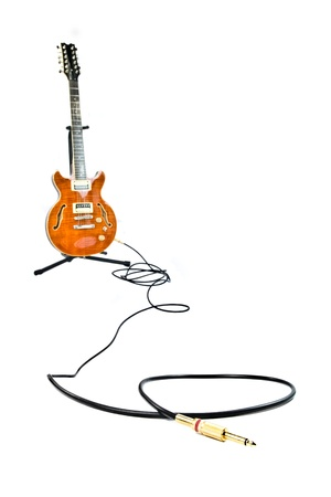 orange electric guitar and cord