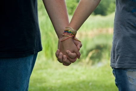 teenage couple holding hands in the park, summer love photo