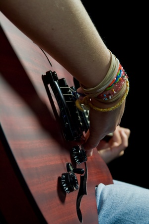 girl playing an electric guitar with black background photo