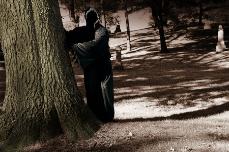 death lurking behind a tree in the cemetery photo