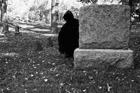spooky graveyard: death lurking behind a gravestone in the cemetery
