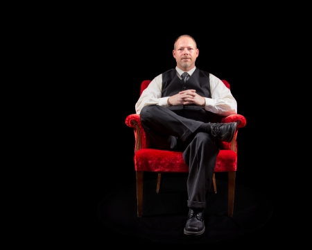 designer chair: successful business man in vest and tie sitting in red velvet chair on black background looking on intently