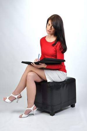pencil skirt: woman in red sweater writing in her notebook