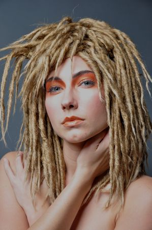 a blond model with dreadlocks and eye makeup