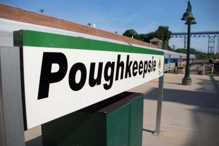 Train station sign for Poughkeepsie, New York.  The sign is White with black lettering with a green stripe across the top from end to end.