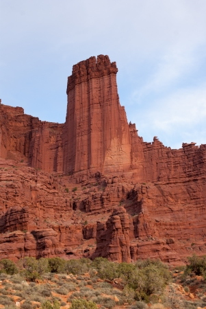 A single rock column juts out above a ridge of red rocks   Behind is a blue sky with whispy white clouds suggesting movement from lower left to upper right