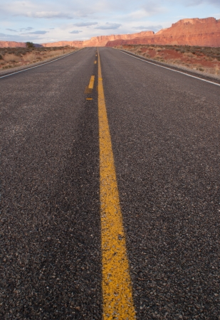 View from a low perspective down the middle of a two lane desert road