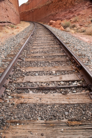 A low angle of a train track disappearing into the distance between two walls of red desert rock  Stock fotó